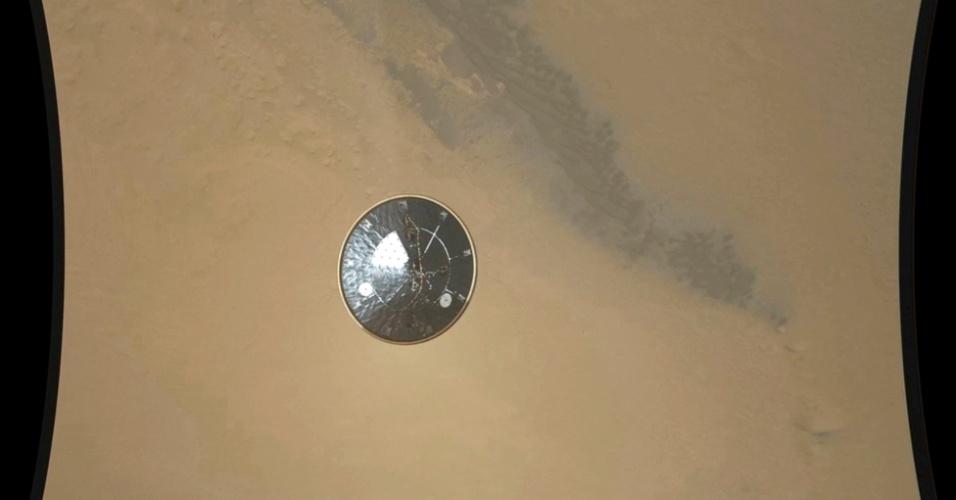 23.ago.2012 -A Nasa (agência espacial norte-americana) divulgou nesta quinta-feira (23) imagem de alta-definição momentos antes do pouso do Curiosity em Marte. O escudo de calor, uma estrutura acoplada ao robô, é ejetada durante a descida ao solo do planeta vermelho