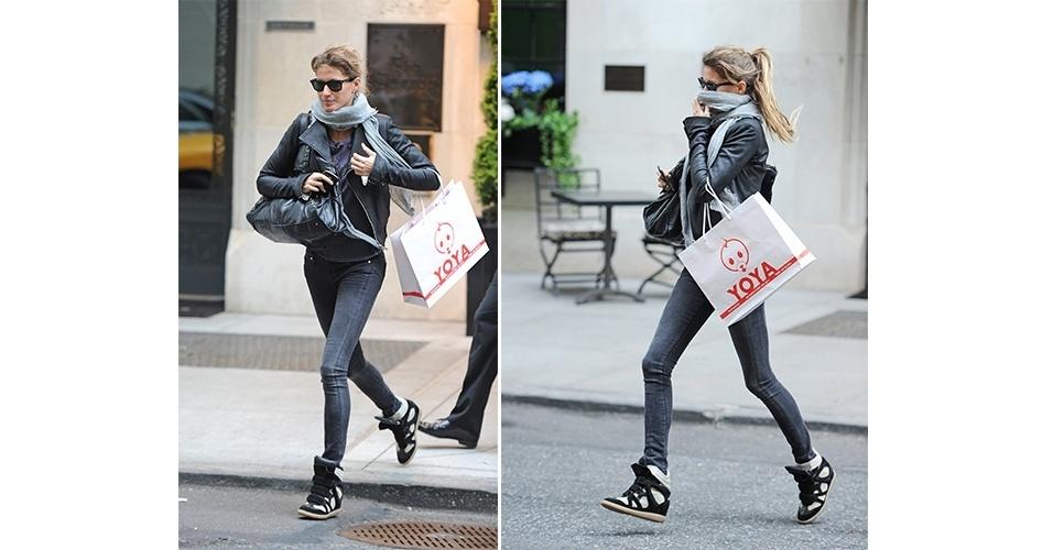 """As pernas finas de Gisele Bündchen valorizaram o sneaker Isabel Marant. A top apostou na combinação básica com calça jeans, camiseta e jaqueta, em tons neutros. O melhor tipo físico para usar tênis com salto embutido é o das magrinhas e bem altas, afinal, por ser volumoso, ele tem a tendência de """"encolher"""" a silhueta"""