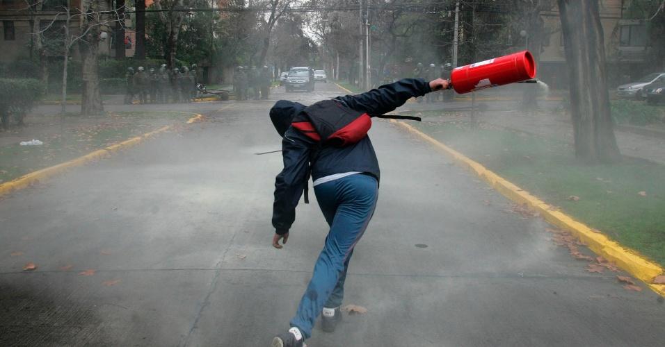 """23.ago.2012 - Estudante chileno atira um extintor de incêndio contra a polícia durante confronto. Os protestos são contra o que os chilenos dizem ser """"especulação no sistema de ensino do Estado"""". Há mais de um ano, alunos têm feito manifestações para pedir mudanças na política educacional do país"""