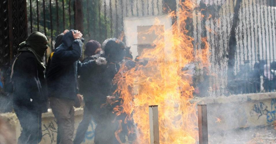 """23.ago.2012 - Estudantes chilenos passam por barricada de fogo durante confronto com a polícia. Os protestos são contra o que os chilenos dizem ser """"especulação no sistema de ensino do Estado"""". Há mais de um ano, alunos têm feito manifestações para pedir mudanças na política educacional do país"""
