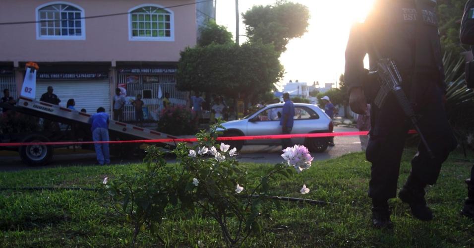 24.ago.2012 - Carro é rebocado de cena de crime, na estrada de Puerto Marquez em Acapulco, no México, após policiais encontrarem o corpo de um homem desmembrado dentro de sacos plásticos no veículo. Segundo a mídia local, a cabeça decepada estava dentro de uma caixa no teto do carro