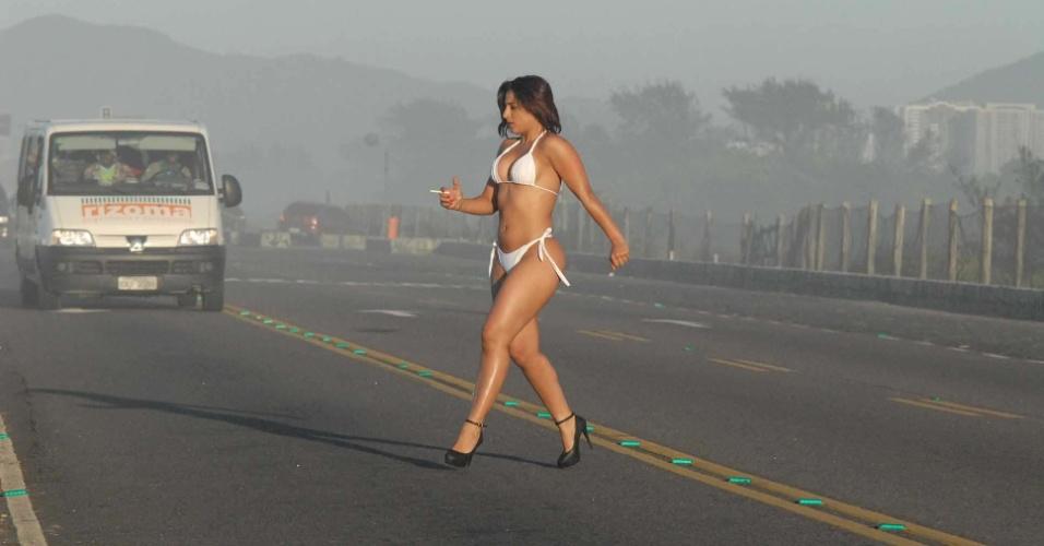 24.ago.2012 - Mulher usando biquini, calçando salto alto e com um cigarro na mão atravessa avenida nesta sexta-feira (24), em frente à praia do Pepê, na zona oeste do Rio de Janeiro (RJ)