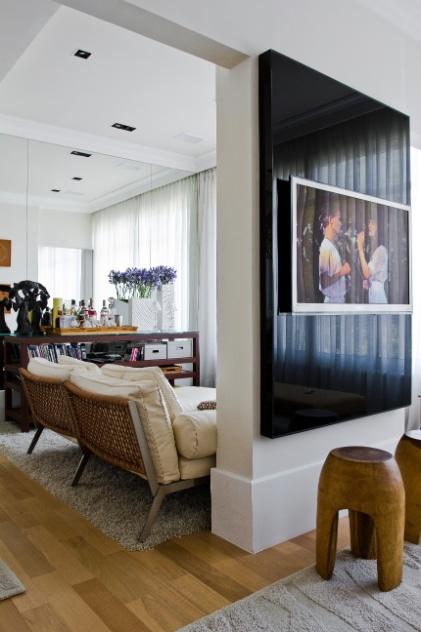 """A parede """"solteira"""" delimita os ambientes e serve de suporte para um painel de madeira e vidro negro que embute a televisão de uma das salas do apê Rio, decorado por Oscar Mikail. À frente do painel, as banquetas tailandesas podem ser encontradas na Cecília Dale"""
