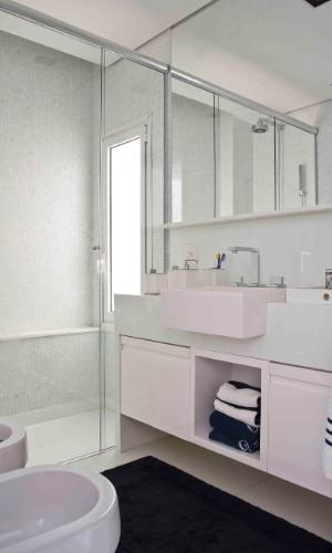 O banheiro da suíte principal do apê Rio é todo branco, com louças, mármore e vidro compondo o espaço. Para dar um charme chique, as toalhas são brancas e azuis, da Trousseau. O apartamento tem reforma e decoração assinadas por Oscar Mikail