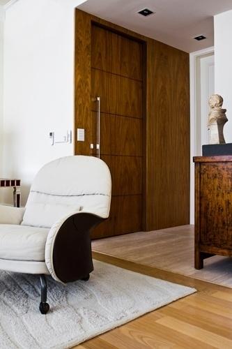 Trocando a porta de entrada de lugar, o arquiteto Oscar Mikail conseguiu criar um pequeno hall de entrada que ganhou elegância com o lambri de freijó que também compõe a porta com puxador da Open. A gostosa poltrona da Casual Móveis se destaca no ambiente social do apê Rio