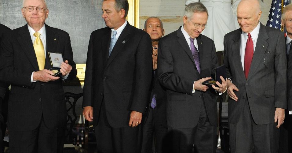 16.nov.2011 - Neil Armstrong (esquerda) recebe medalha do Congresso dos Estados Unidos. Na ocasião, seus companheiros de missão (Michael Collins e Buzz Aldrin), também foram lembrados pelo feito de serem os primeiros homens a terem pisado na lua. Na imagem também está John Glenn (segurando uma placa no lado direito), que foi o primeiro homem a fazer um voo em órbita da Terra