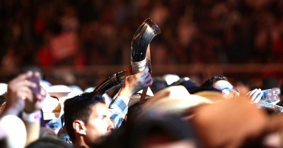 Membro do público mostra seu berrante durante apresentação de Fernando & Sorocaba