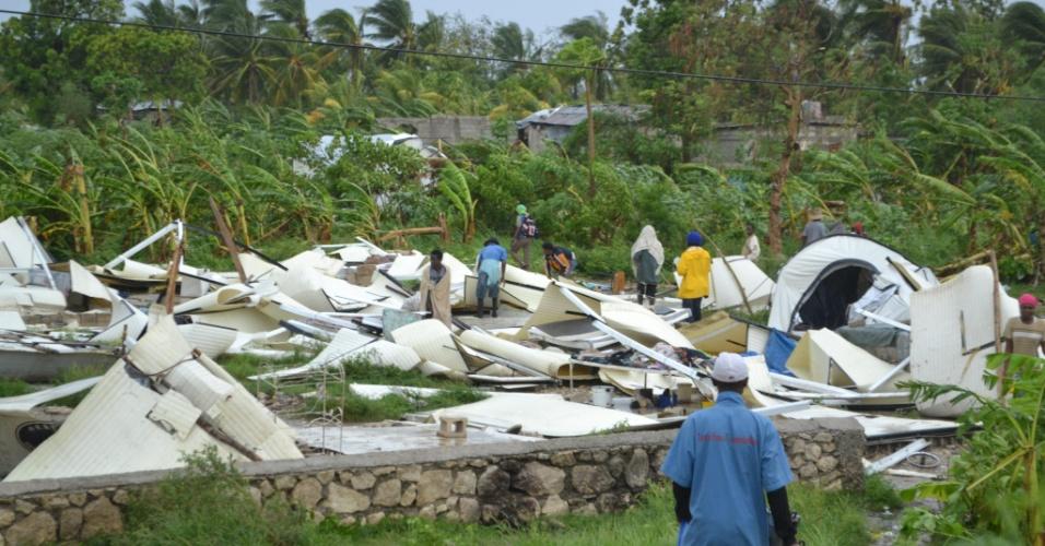 25.ago.2012 - Moradores inspecionam os restos de um acampamento dedicado aos desabrigados mas que ficou totalmente destruído após a passagem da tempestade tropical Isaac em Porto Príncipe, no Haiti