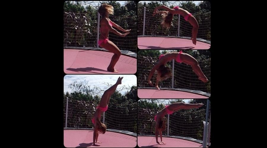 De biquíni, Carolina Dieckmann fez acrobacias em uma cama elástica (26/8/12)