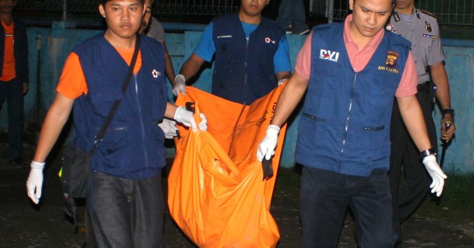 27.ago.2012 - Bombeiros resgatam o corpo de uma das vítimas de um acidente de avião na ilha de Borneo, na Indonésia. Um avião de pequeno porte caiu no local, nesta segunda-feira (27). Foram encontrados o corpo de um australiano de doutros três homens ainda não identificados