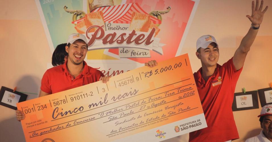 27.ago.2012 -  Os donos da barraca Pasteis Kyoto recebem o cheque e comemoram o título de melhor pastel de São Paulo, no concurso realizado nesta segunda-feira (27), na feira da Praça Charles Miller, no bairro do Pacaembu