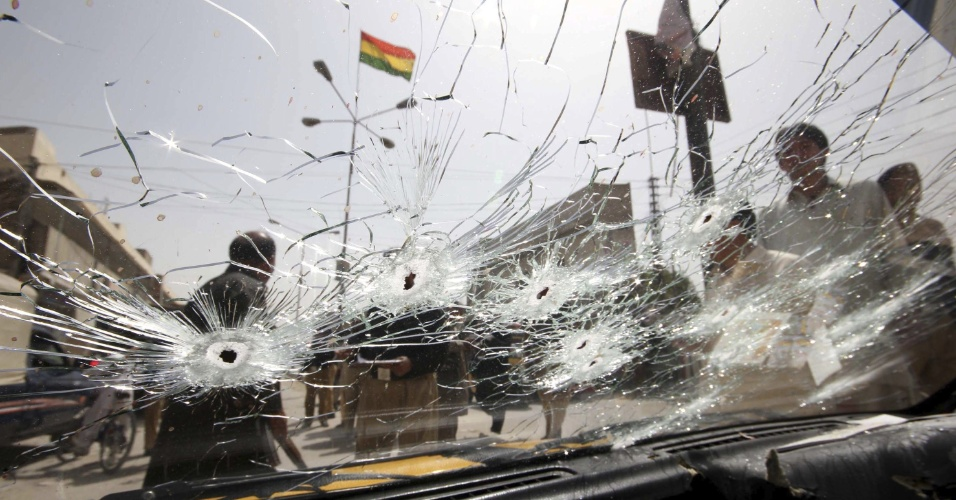 27.ago.2012 - Policial inspeciona táxi que foi alvo de balas em Quetta, na província de Baluchistán, no Paquistão, nesta segunda-feira (27). Segundo a imprensa local, ao menos três pessoas morreram após criminosos atirarem contra o veículo. O caso será investigado