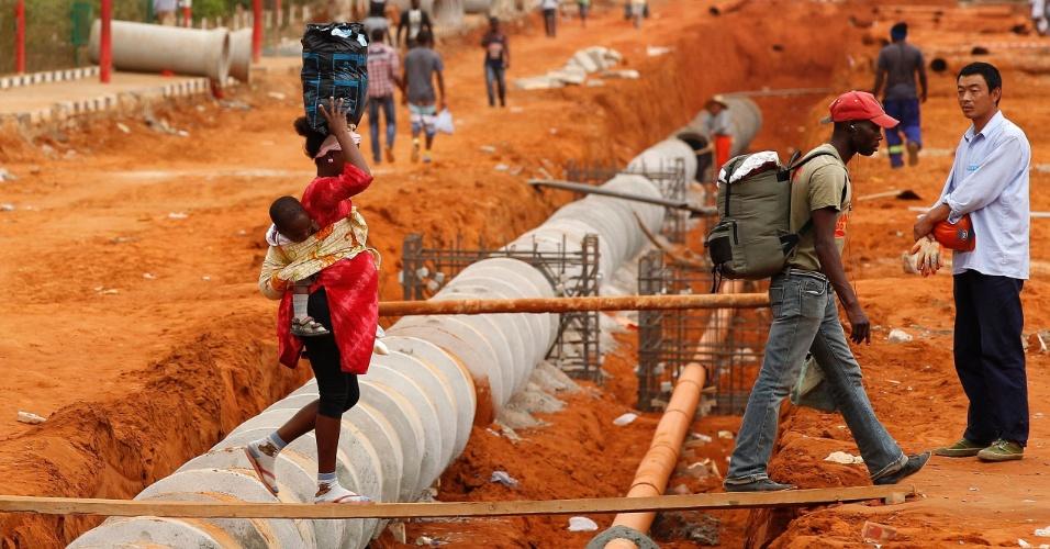 http://imguol.com/2012/08/27/27ago2012---trabalhador-chines-cruza-ponte-improvisada-em-viana-cidade-localizada-na-regiao-de-luanda-em-angola-1346107961177_956x500.jpg