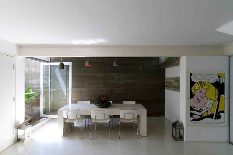 A área social da casa, a despeito de ser um sobrado geminado, recebe luz natural de todas as direções possíveis. Refletida pelo piso epóxi (Delta Pisos), que vai até a cozinha, e difundida através uma arquitetura com interiores de linhas retas e muito limpa, essa luz se potencializa ainda mais. O rústico se integra ao branco contínuo instaurado na reforma da Casa Cayowaa pelo arquiteto Franscico Spadoni