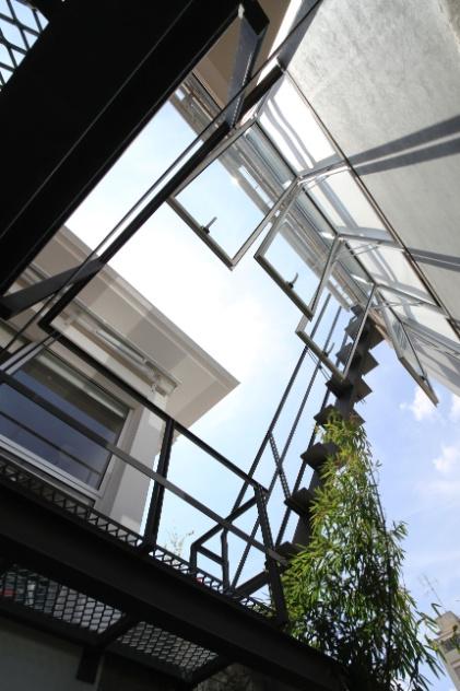 """A caixilharia de alumínio (Projeto Envidraçamentos) em todo o pavimento superior - e também na abertura que liga a sala de TV à passarela - foi desenvolvida em alumínio, sob medida, com persianas rolô. São janelas """"máximo ar"""" e portas de correr. Lateral à passarela, está uma escada metálica (Açotech), que leva à cobertura sobre o quarto do filho do casal, na edícula. A reforma da Casa Cayowaa é assinada por Francisco Spadoni"""