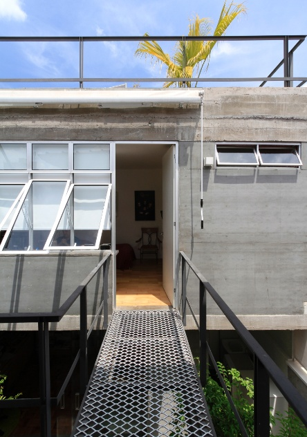 """A passarela metálica (Açotech) fica ancorada nas lajes de concreto da Casa Cayowaa, cujo projeto de reforma é de Francisco Spadoni. O novo quarto do filho do casal teve sua parede externa revestida de placa cimentícia Eternit 10 mm (espessura), que é parafusada diretamente na alvenaria. A mesma parede tem uma testeira (parte superior, onde o toldo está fixado) de concreto moldado """"in loco"""" - trata-se do ponto de união entre a laje e a viga de concreto da cobertura"""
