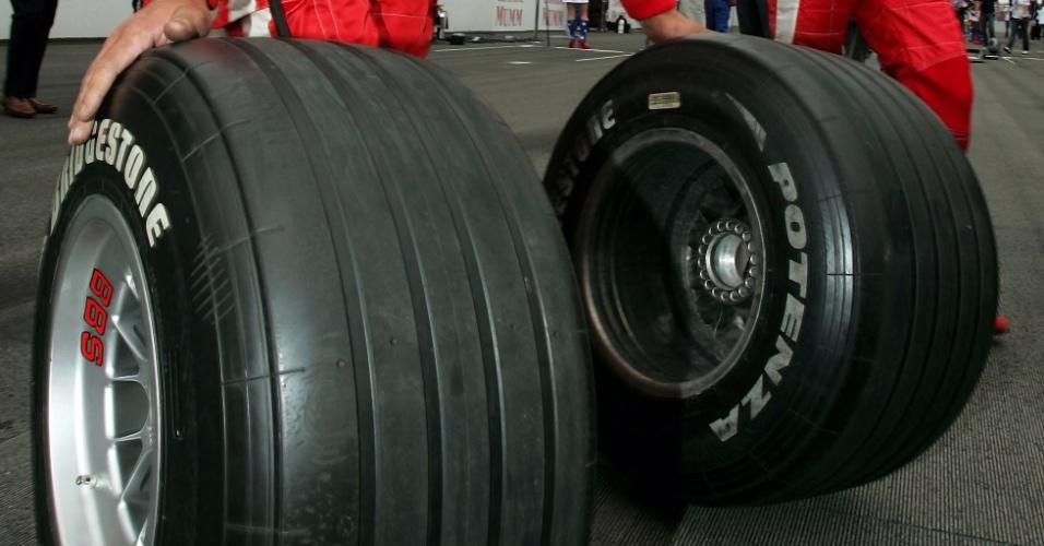 Ao lado de Schumacher, mecânico da Ferrari carrega pneus durante o GP dos Estados Unidos de 2005