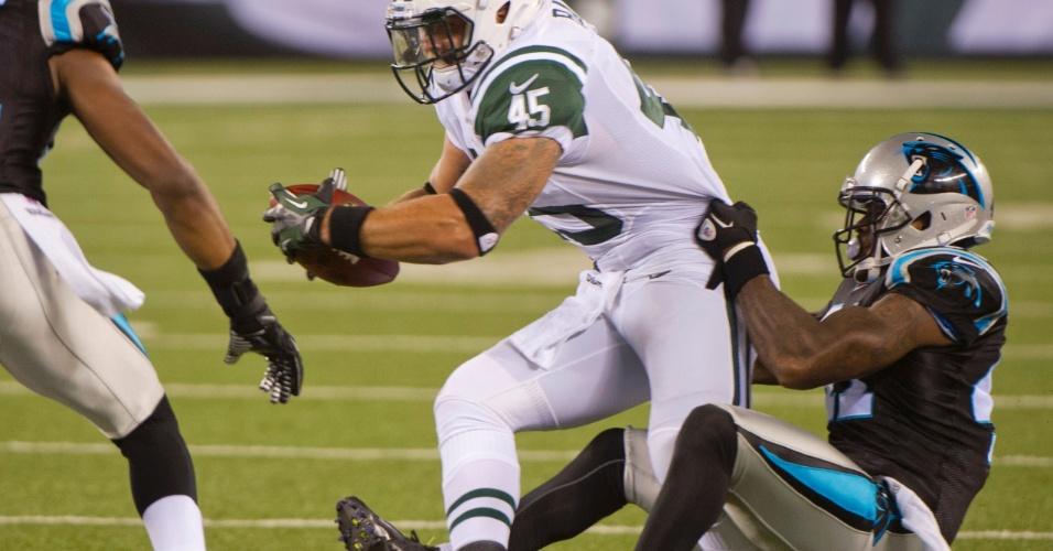 Captain Munnerlyn (dir.), do Carolina Panthers, faz de tudo para parar o rival Josh Baker, do New York Jets, segurando-o até pela cintura (26/08/2012)
