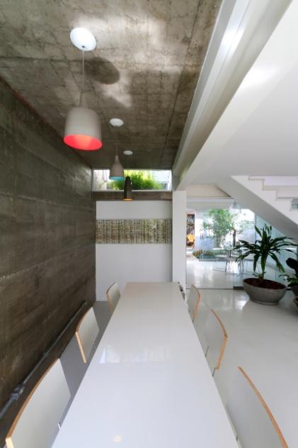 Em todo o interior integrado - estar, jantar e cozinha -, o piso é de epóxi branco (Delta Pisos). Sobre a mesa de jantar, as luminárias são da Bertolucci e, ao redor do móvel, estão as cadeiras de Fernando Jaeger. O projeto que remodelou a Casa Cayowaa é de Francisco Spadoni