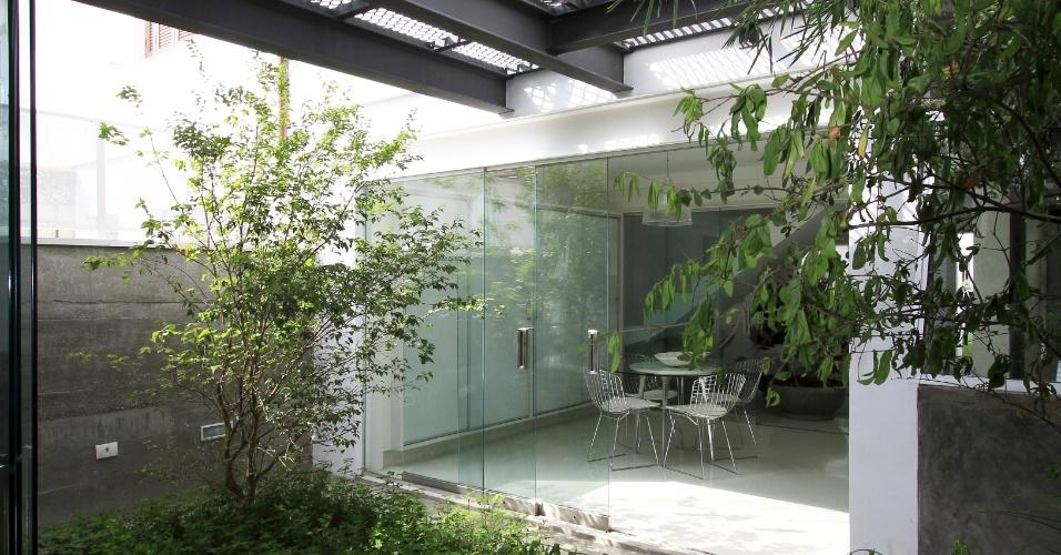 No quintal da Casa Cayowaa, entre os dois volumes construídos há um jardim. O espaço tem paisagismo de Célia Alves e piso em cimento queimado. A reforma da residência foi idealizada pelo arquiteto Francisco Spadoni