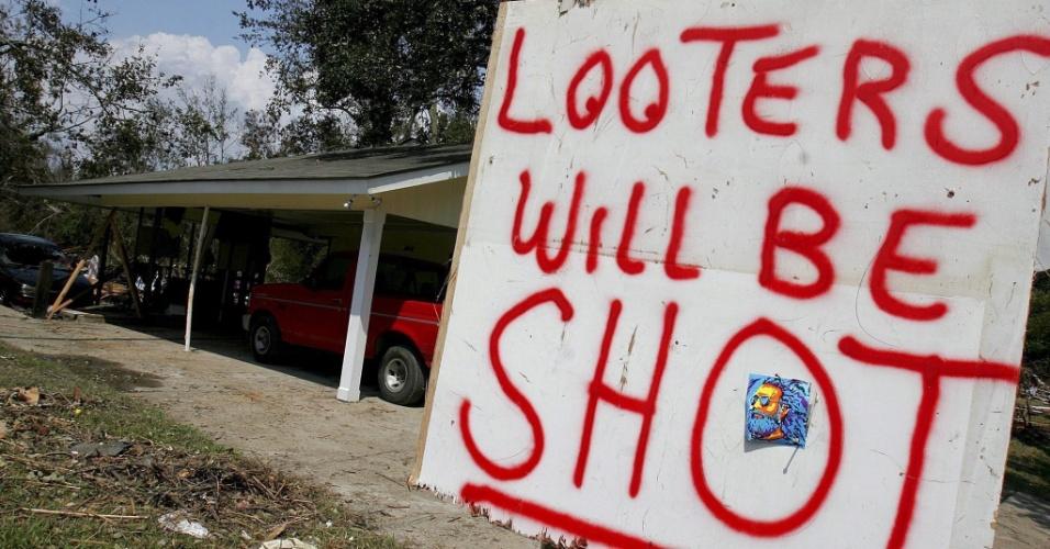 1.set.2005 - Cartaz adverte saqueadores em bairro alagado em Pascagoula, no Mississippi (EUA) após passagem do furacão Katrina: