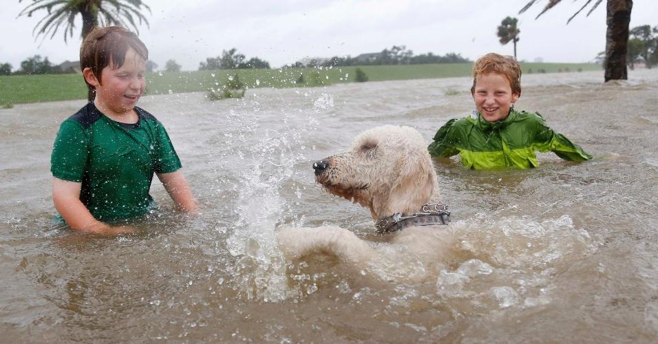 28.ago.2012 - Joshua Keegan (à esq.) e Ruffin Henry, ambos com 10 anos, brincam com o cachorro Keegan em área alagada pelo furacão Isaac no lago Pontchartrain, em Nova Orleans, no Estado de Louisiana