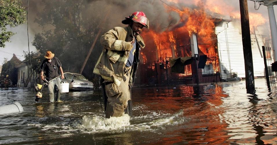 6.set.2005 - Bombeiro ajuda morador a sair da água enquanto casa pega fogo, em Nova Orleans (EUA) depois da passagem do furacão Katrina pela cidade. Com a água começando a baixar na cidade, corpos de vítimas do desastre vieram à tona, alguns em avançado estado de putrefação