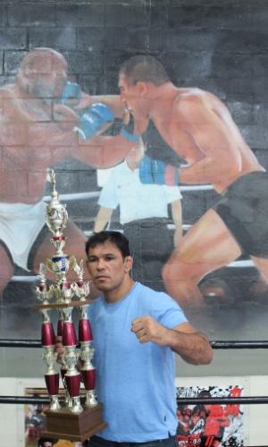 Rodrigo Minotauro com uma imagem de seu épico duelo com Bob Sapp ao fundo