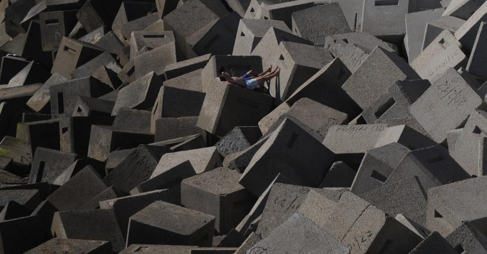 29.ago.2012 - Dois garotos tomam sol em blocos de concreto em praia de Cadiz, na Espanha