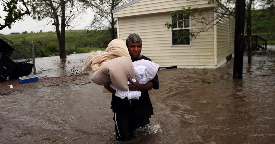 29.ago.2012 - Homem retira pertences de casa enquanto sobe o nível da água em bairro alagado pela passagem do furacão Isaac, em Oakville, no estado de Louisiana (EUA). O Isaac perdeu intensidade e voltou a ser classificado como tempestade tropical. No entanto, ele continua causando fortes chuvas