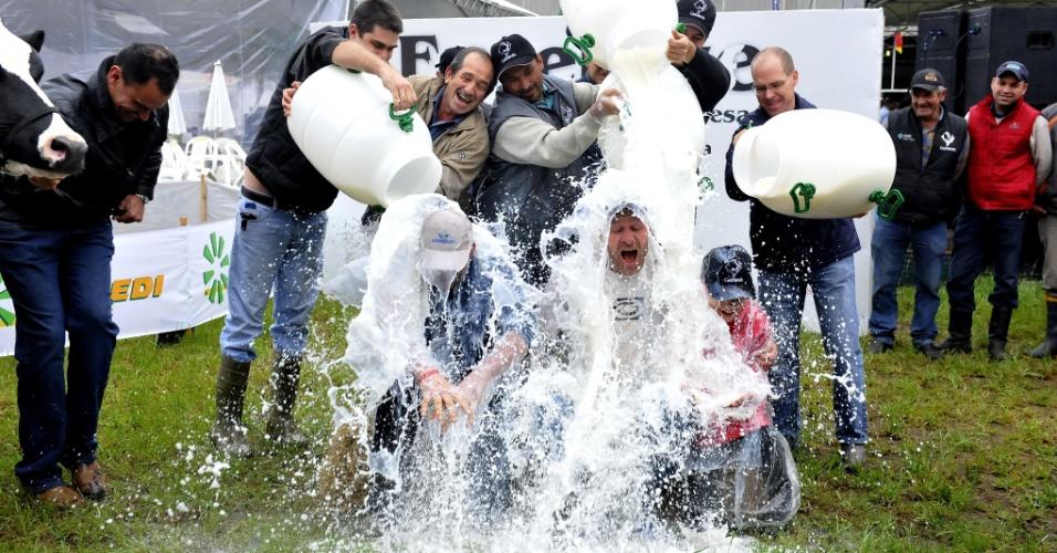 29.ago.2012 - Itamar Tang, 42, proprietário da Granja Tang, toma banho de leite após vencer, pelo segundo ano consecutivo, o concurso Leiteiro da Raça Holandesa da Expointer