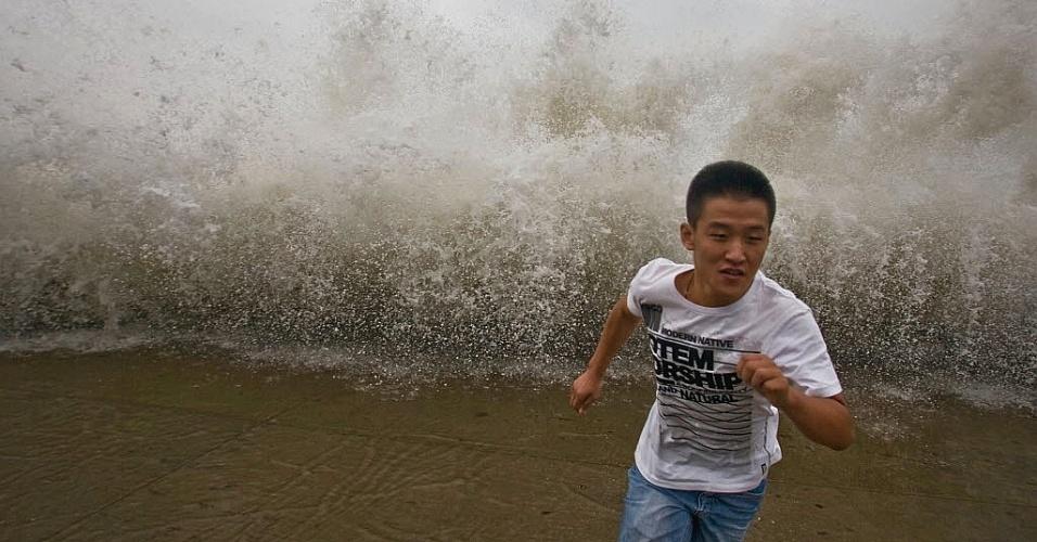 29.ago.2012 - Rapaz corre para não ter atingido por onda gigante em Qingdao, na China, provocada pela passagem do tufão Bolaven pela região