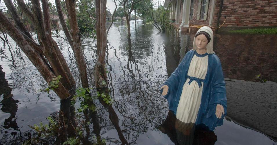 30.ago.2012 - Estátua da Virgem Maria permanence em pé em jardim de casa alagada pela tempestade tropical Isaac em La Place, na Louisiana, nesta quinta-feira (30)