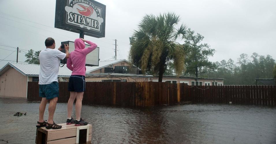 30.ago.2012 - O casal Hank e Lori Plauch observam a cheia de um rio inundar as imediações do restaurante Seafood, do qual são donos, em Kiln, no Mississippi (EUA). As inundações foram provocadas pela passagem do furacão Isaac pelo Estado