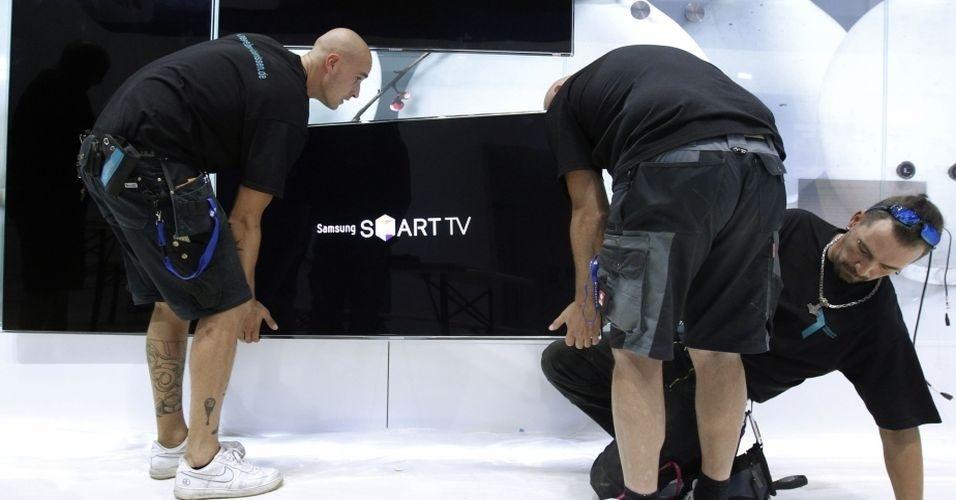 Junto como smartphones, tablets, computadores e outros gadgets, a tecnologia das TVs também chama atenção na IFA 2012. Na foto, trabalhadores montam estande da Samsung com aparelhos da linha Smart TV