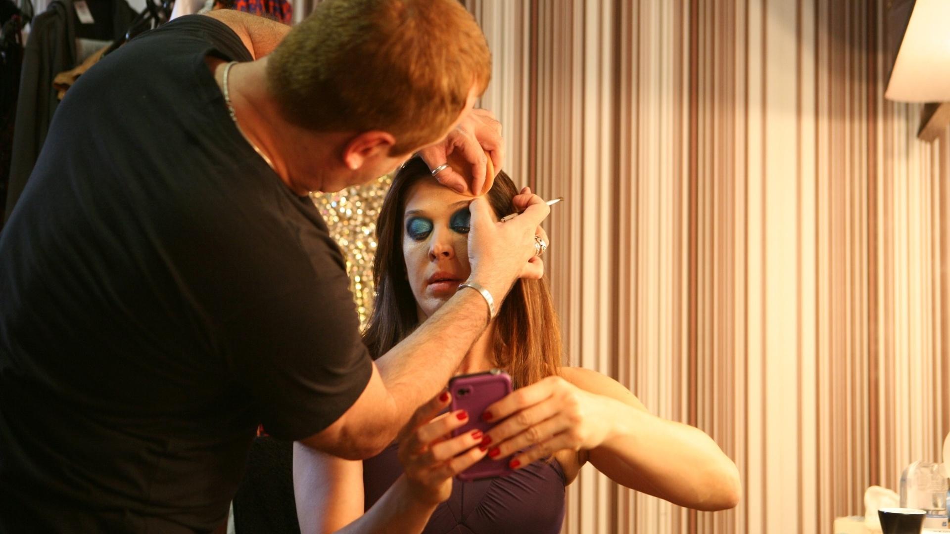 Cláudia Raia confere suas mensagens enquanto se maquia pouco antes da reestreia do musical
