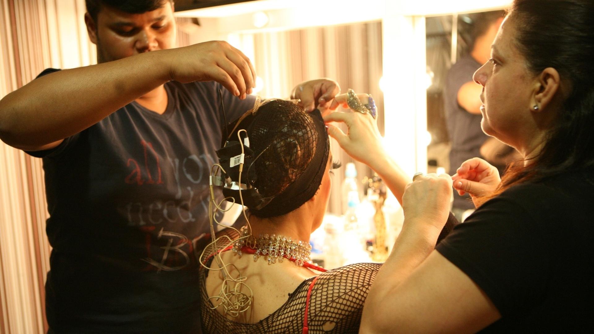 Cláudia Raia ajusta microfone e coloca a peruca de sua personagem Sally Bowles pouco antes de entrar em cena na reestreia do musical
