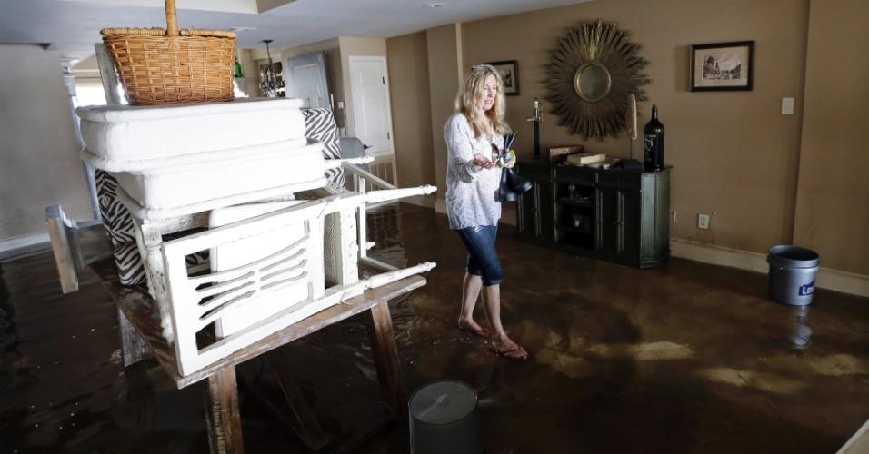 31.ago.2012 - Mulher anda no interior de casa inundada após quebra de barragem em Braithwaite, Louisiana (EUA), nesta sexta-feira (31). Os moradores de cidades afetadas pelo furacão Isaac começaram a contabilizar os danos e recuperar seus pertences, mas muitas casas permanecem alagadas e sem energia elétrica