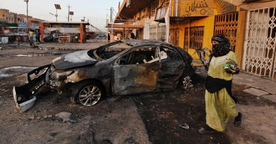 2.set.2012 - Mulher caminha por local onde aconteceu um ataque com carro-bomba neste domingo (2), em Bagdá, no Iraque