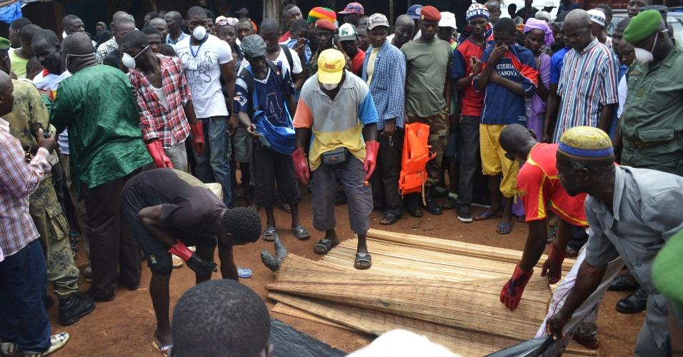 Grupos de homens observa um corpo encontrado no mar neste domingo (2), em Conracri, Guiné. Cerca de 30 pessoas estavam em um barco que naufragou na costa do país. Segundo informações das autoridades locais, a equipe de resgate já não possuía mais esperança de encontrar sobreviventes desde sábado (1)