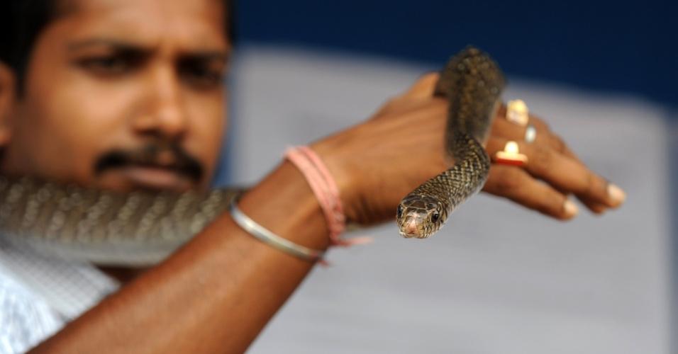 Um homem segura uma cobra durante a campanha de conscientização em Siliguri, Índia, neste domingo (2). O objetivo da ação é auxiliar a população local em relação a convivência com os animais