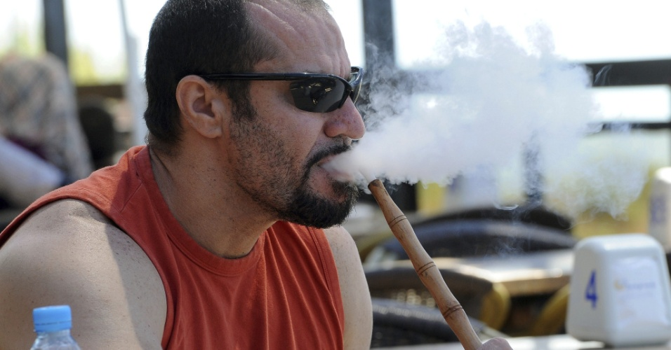 Um libanês fuma um cachimbo de água em um bar em Beirute, no Líbano, neste domingo (2). O parlamento libanês aprovou uma lei que proíbe o fumo em locais públicos, incluindo bares, restaurantes, e escritórios. A medida passa a valer nesta segunda-feira (3)