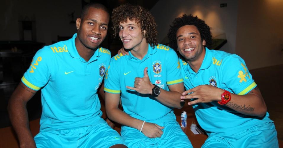 Jogadores da seleção têm momento de descontração no CT de Cotia. Os zagueiros Dedé e David Luiz e o lateral esquerdo Marcelo brincam na apresentação da seleção