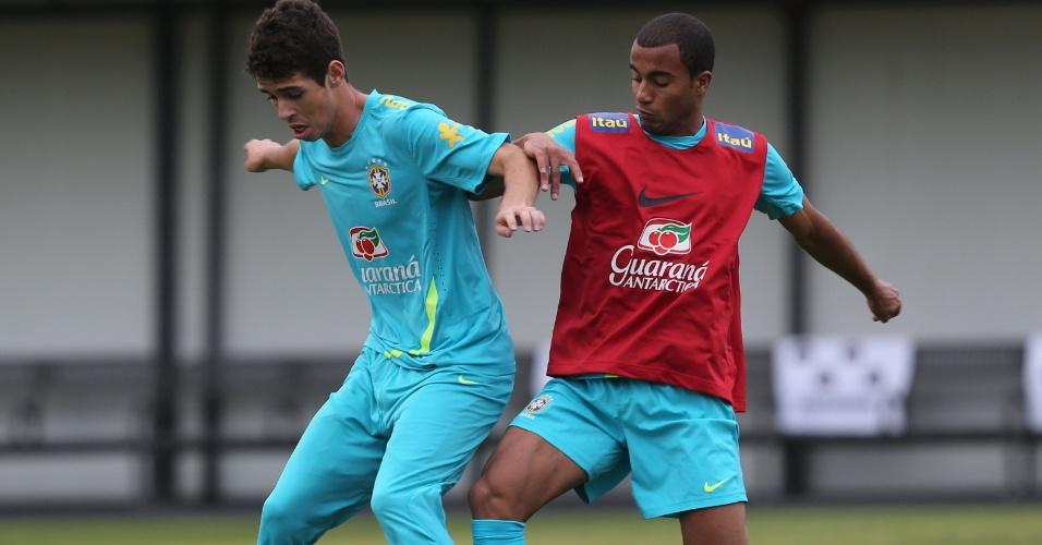 Marcado por Lucas, Oscar tenta proteger a bola durante treino realizado pela seleção brasileira em Cotia