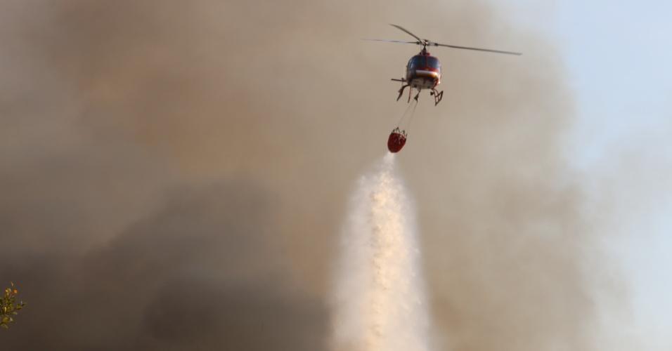 5.set.2012 - Bombeiros tentam conter incêndio com a ajuda de um helicóptero em um terreno particular próximo à Praia da Daniela, em Florianópolis. O fogo atingiu cerca de 20 hectares