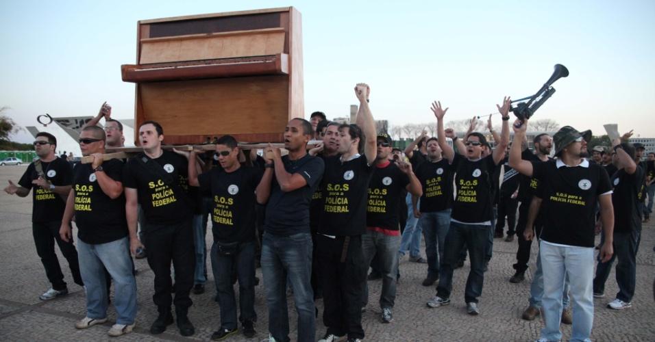 5.set.2012 - Policiais federais carregam piano nas costas durante novo protesto realizado na Praça dos Três Poderes, em Brasília. A classe continua de greve