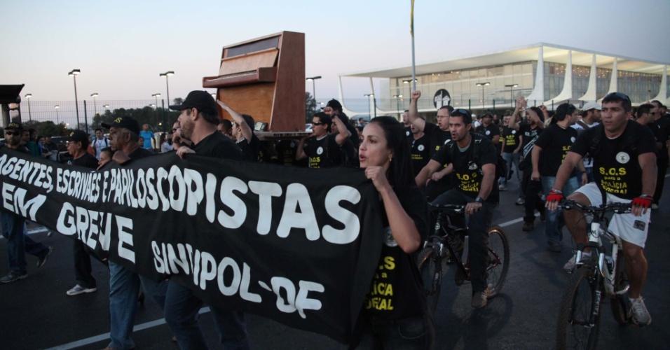 5.set.2012 - Servidores da Polícia Federal exibem cartazes e carregam piano nas costas durante protesto realizado na Praça dos Três Poderes, em Brasília. A categoria continua de greve