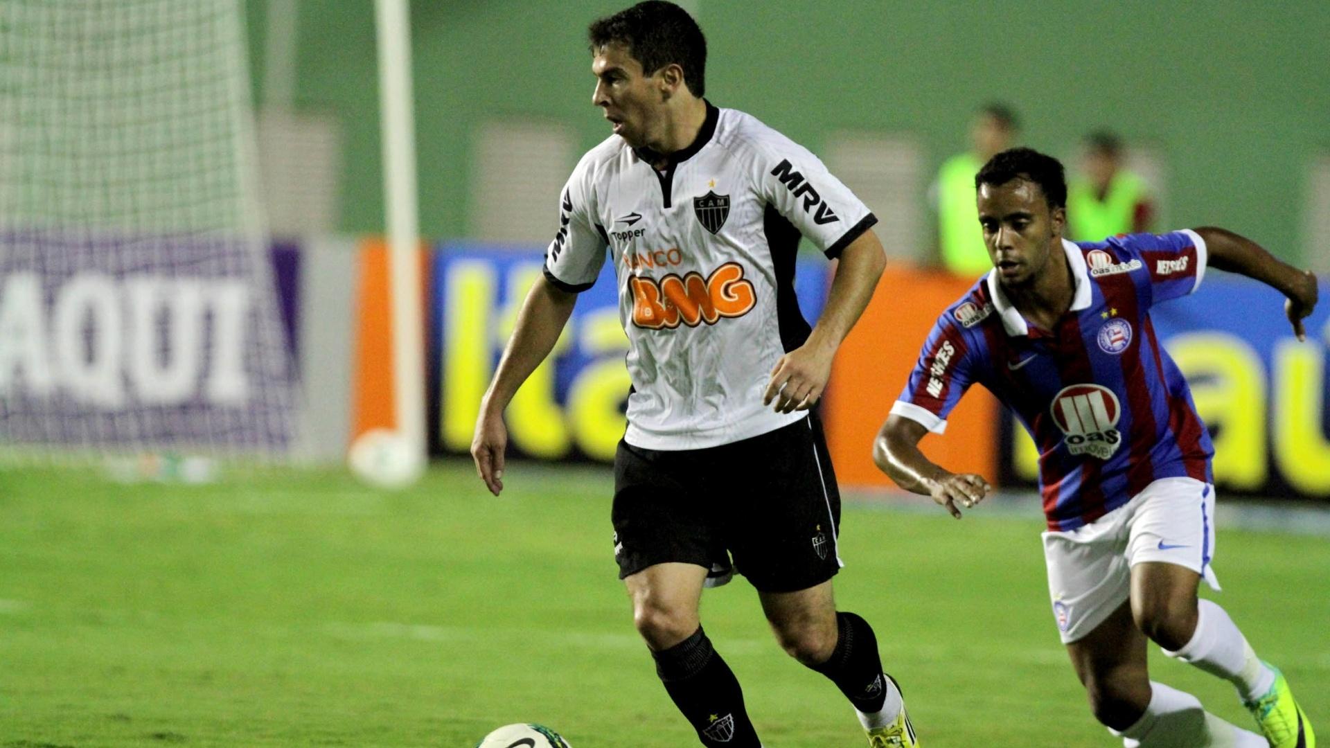 Leandro Donizete, do Atlético-MG, conduz a bola e é perseguido por Romário, do Bahia