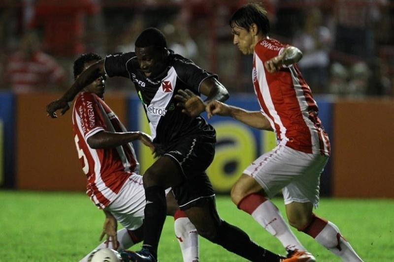 Tenório, atacante do Vasco, tenta passar por dois marcadores do Náutico durante partida nos Aflitos