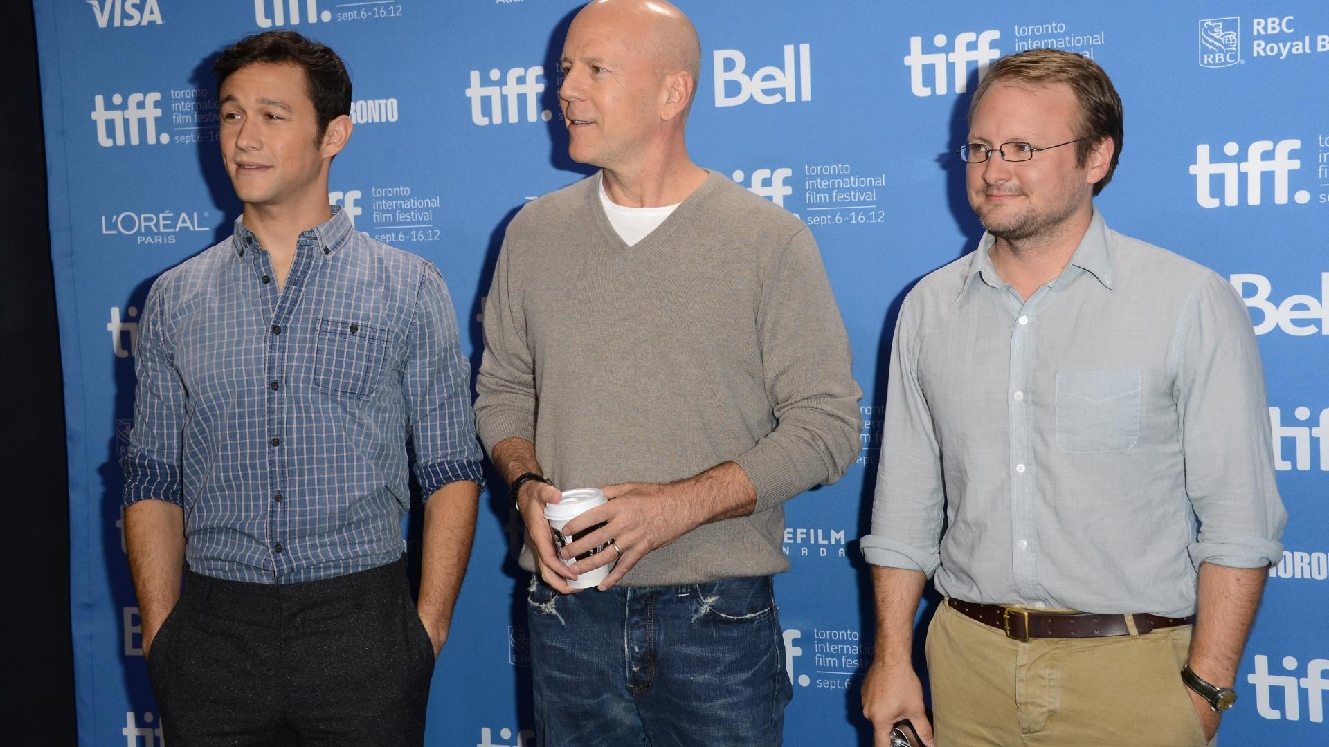 Da esquerda para a direita: os atores Joseph Gordon-Levitt, Bruce Willis e o diretor Rian Johnson dão entrevistas sobre o filme